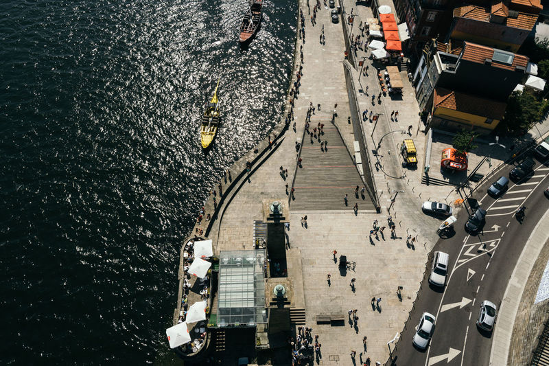 High angle view of people on street by river in city during sunny day
