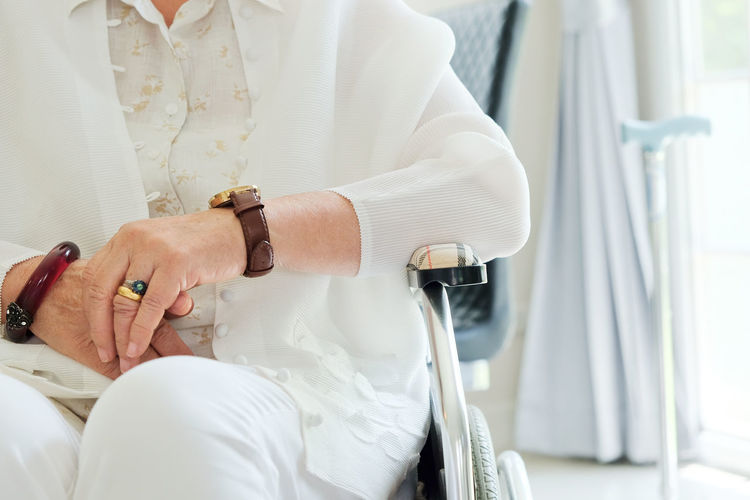 Midsection Of Woman Sitting On Wheelchair