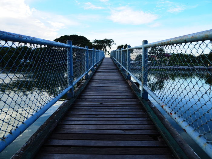 Empty footbridge over lake against sky