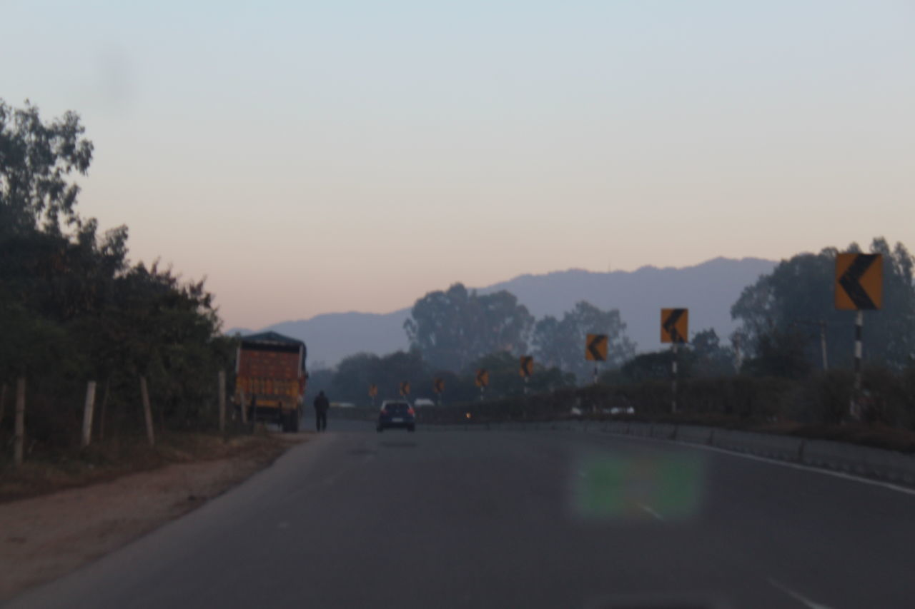 ROAD BY CITY AGAINST CLEAR SKY