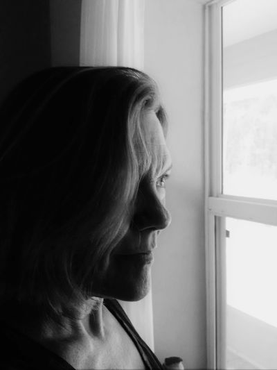 Side view of mature woman looking through window at home