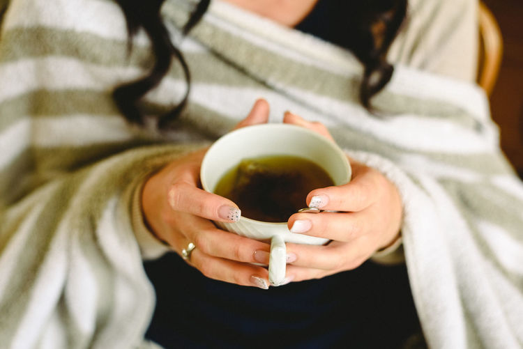 Midsection of woman holding black tea