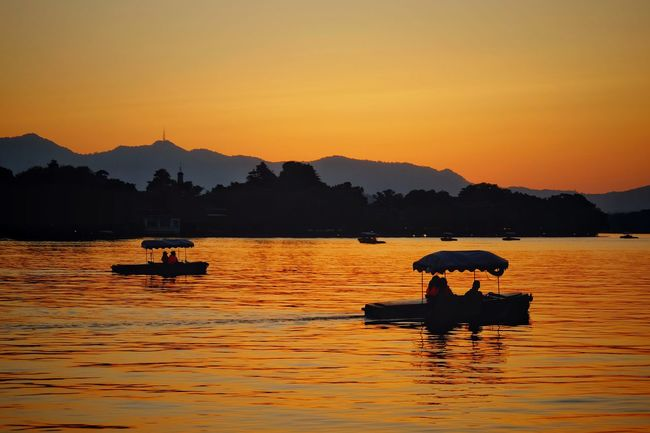 Sunset Lake Silhouette Reflection Water Mountain Outdoors Landscape Night Beauty In Nature Summer Boat Silhouette Mountain Range Travel Warm Glow Vacations Light And Shadow Hangzhou,China West Lake, Hangzhou Lake View Yellow China View Scenics Travel Destinations