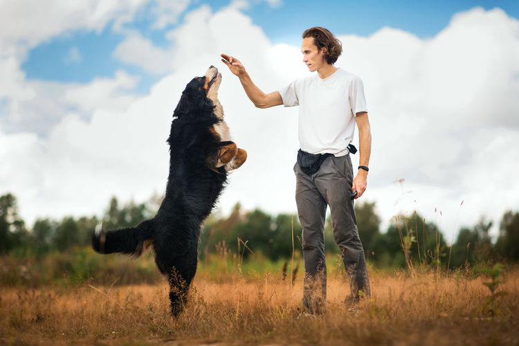Full length of man with dog on field
