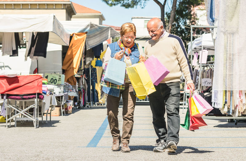 Senior Couple Holding Shopping Bags On Street In City