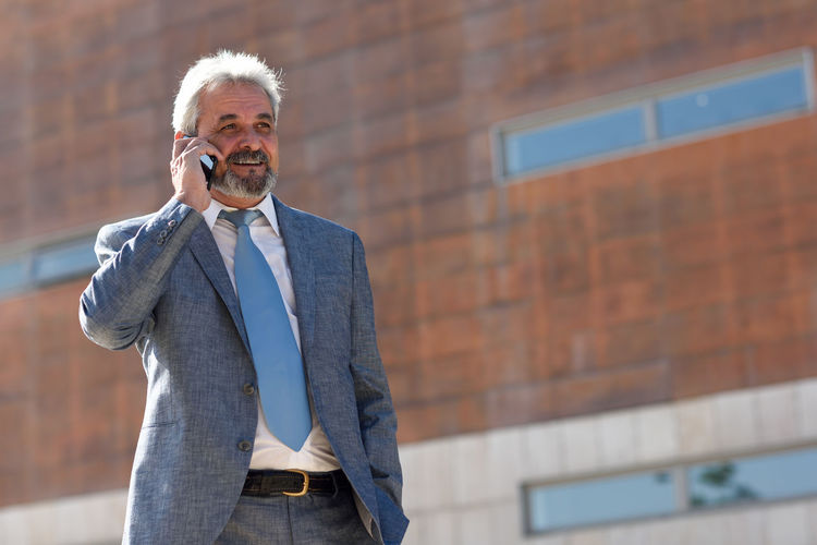 Mature man using mobile phone while standing outdoors