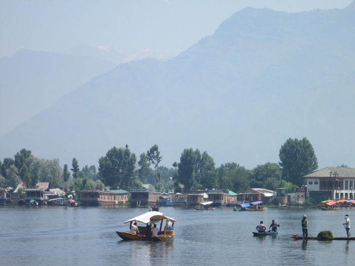 People Boating On River Against Mountain During Foggy Weather