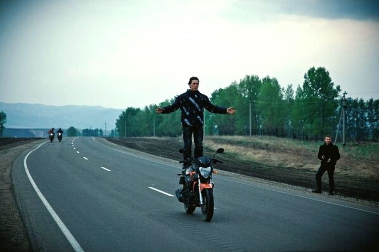 Full length of man riding motorcycle on road