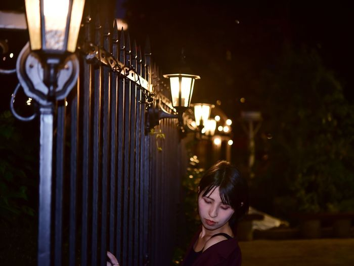 Close-up of woman standing by illuminated lamp at night