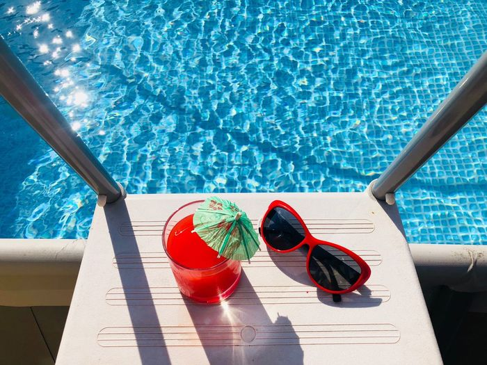 High angle view of drink with sunglasses on steps over swimming pool