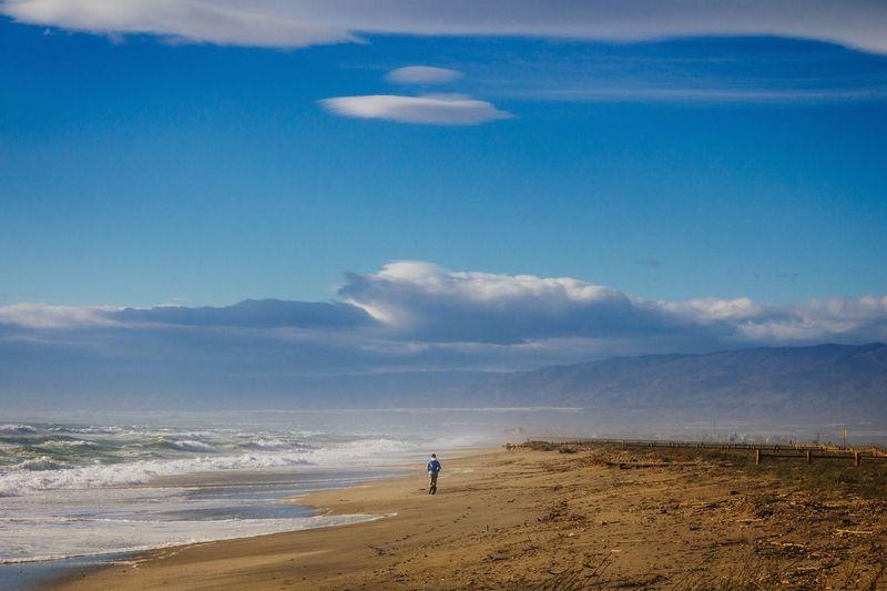 Rear view of a man walking on calm beach