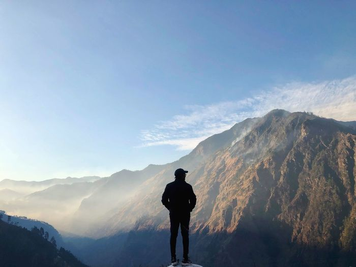 Rear view of silhouette man standing on mountain against sky