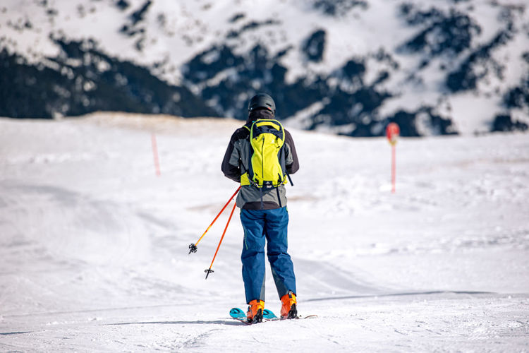 Rear view of person with umbrella on snowcapped mountain