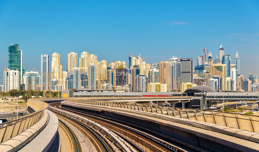 Railroad tracks amidst buildings in city against clear sky