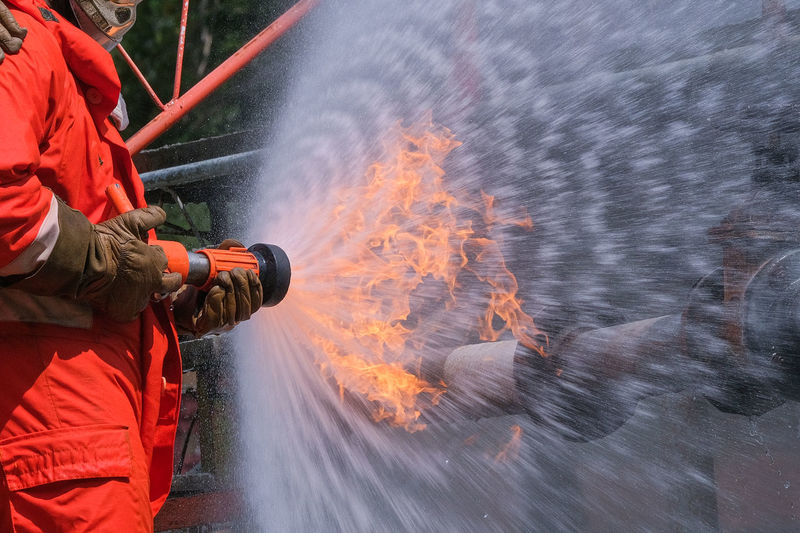 Midsection of firefighter spraying water