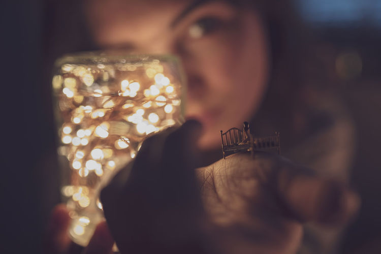 Close-up portrait of woman holding illuminated lighting equipment and miniature toy
