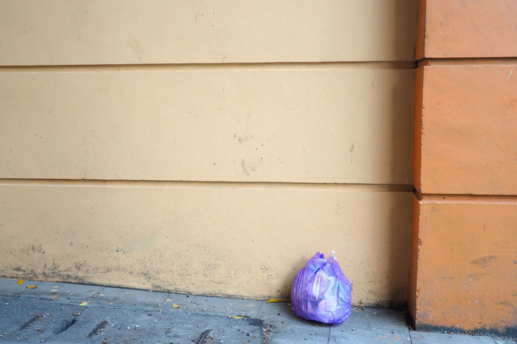 Garbage on wall by footpath against building