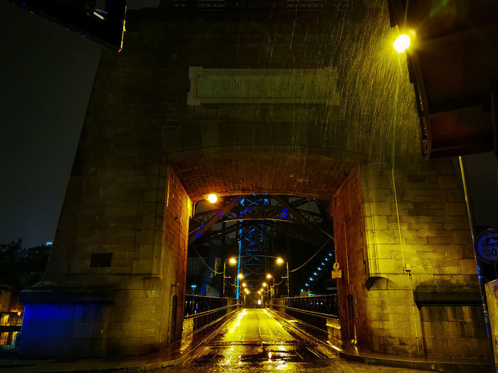 Illuminated bridge over road at night