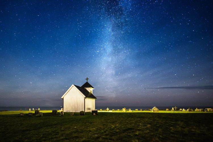 Church on grass against sky at night