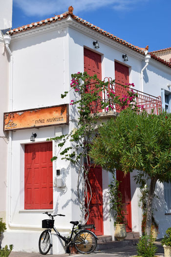 Greek islands' architecture Entrance Greek Islands Sunny Architecture Bicycle Blue Sky Building Building Exterior Built Structure Cycling Day House Nature No People Outdoors Plant Potted Plant Red Summer Sunlight Transportation Travel Destinations Tree Window Windowframe