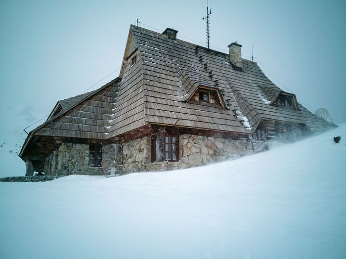 Low angle view of snow covered building against sky