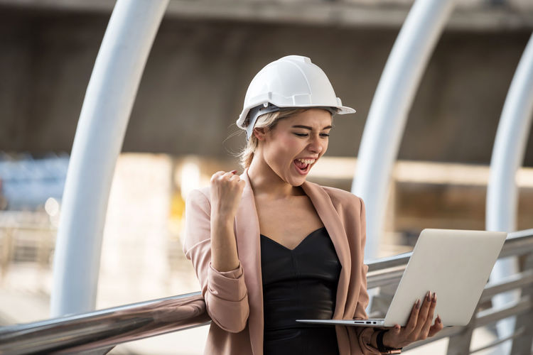 Happy architect looking at laptop while standing by railing