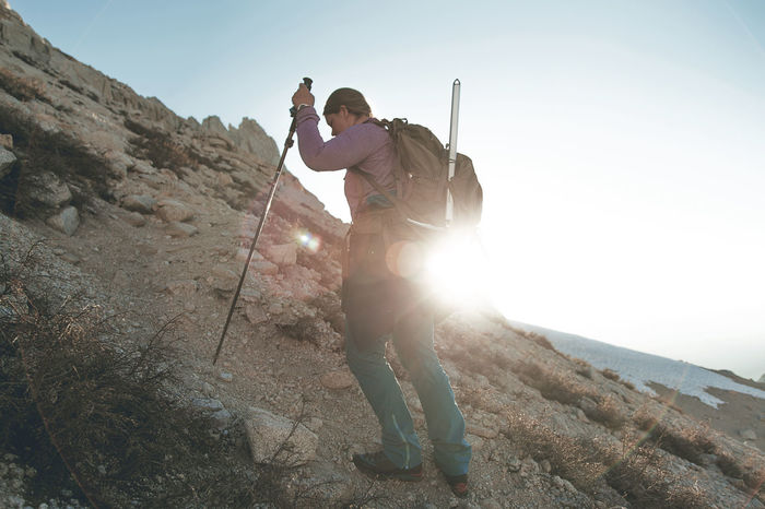 Mid adult woman hiking on mountain against sky