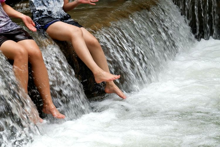 Low section of women enjoying at waterfall
