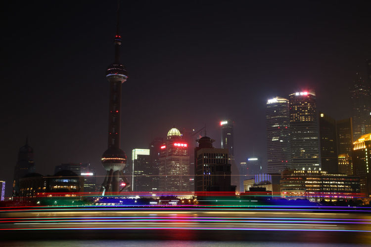 Light Trails On Huangpu River Against Illuminated City Against Sky
