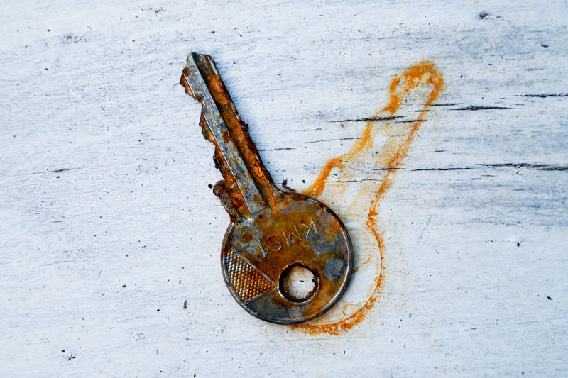 Directly above shot of rusty key and stain on wooden table