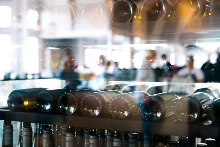 Reflection of wine in glass bottles on shelf at restaurant