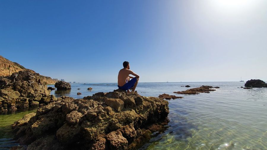 Man standing on rock by sea against clear blue sky