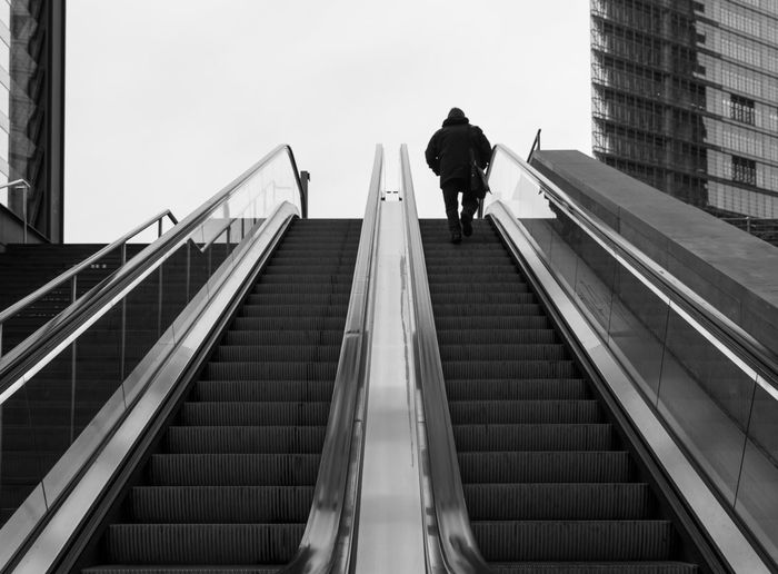 Low angle view of man moving up on escalator against sky