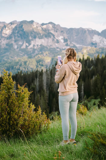 Full length of woman photographing on mountain