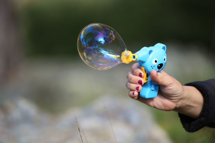 Close-up of woman hand making bubble from wand
