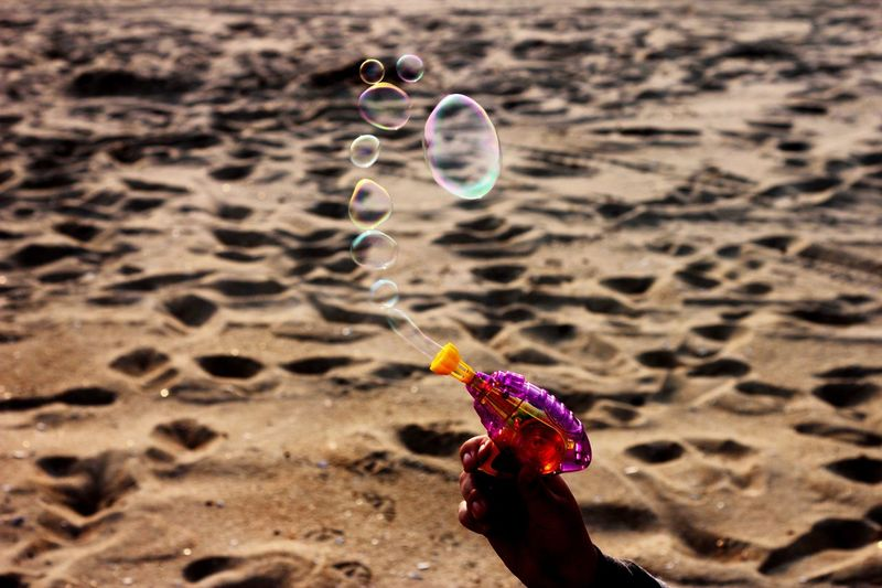 Bubbles coming out of a toy gun Toy Gun Land Sand Beach Nature Fragility Focus On Foreground Vulnerability  Bubble Day Sunlight Close-up Mid-air Beauty In Nature Outdoors Motion No People Selective Focus