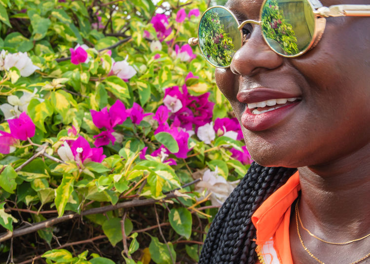 African woman with round glasses from ghana stands with joy at beautiful flowers in accra