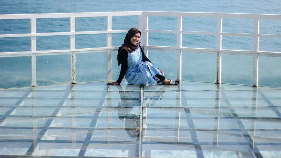 Portrait of smiling woman sitting by railing against sea
