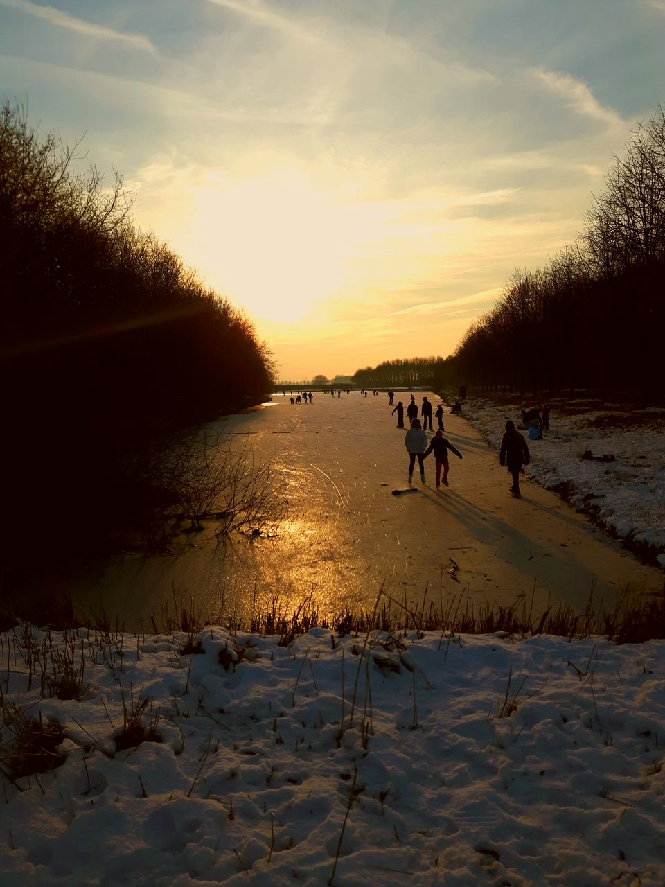 sunset, nature, winter, domestic animals, sky, beauty in nature, cold temperature, mammal, snow, scenics, silhouette, sun, sunlight, outdoors, tree, real people, dog, togetherness, men, water, day, people