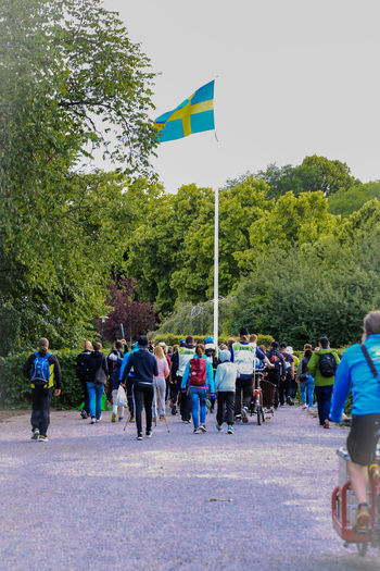 Sweden Adult Crowd Day Flag Flags Flags In The Wind  Green Color Group Of People Large Group Of People Leisure Activity Lifestyles Men Nature Outdoors Plant Race Real People Road Sport Transportation Tree Walking Walking Group Women