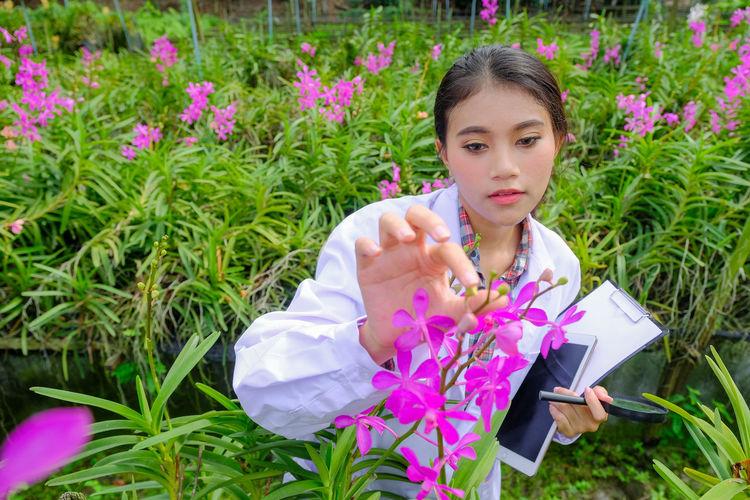 Portrait of woman holding pink flower on field