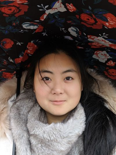 Close-up portrait of smiling woman wearing warm clothing while lying on bed at home