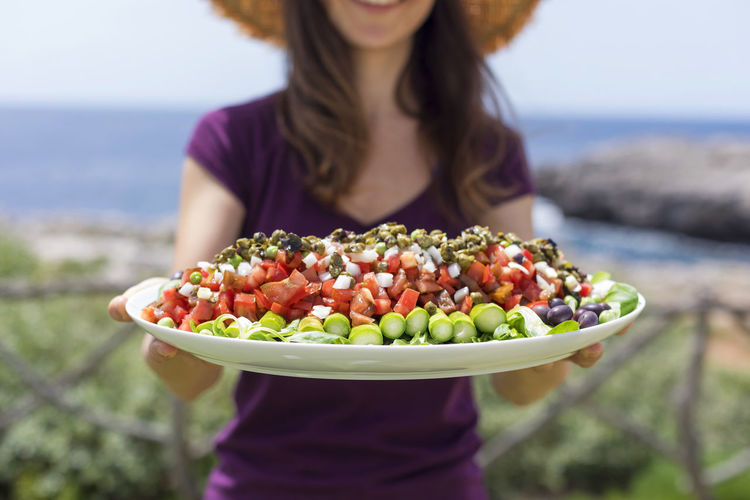 Midsection of woman holding food outdoors