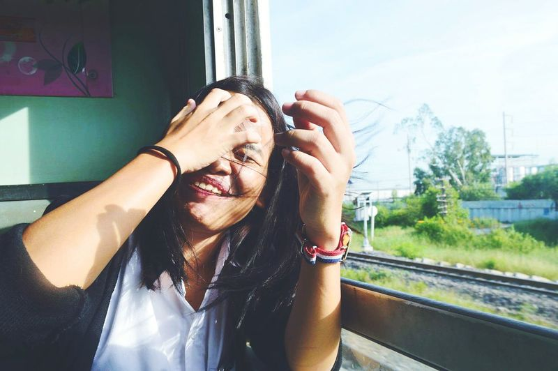 Smiling woman sitting by window in train