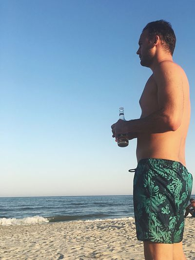 Midsection of shirtless man standing at beach against clear sky
