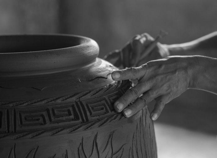 Close-up of potter carving pot at workshop