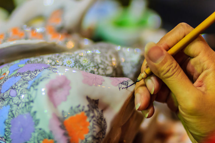 Cropped image of artist painting on ceramics