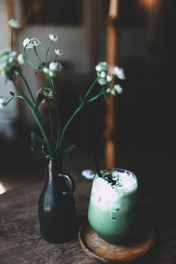 Close-up of flowers in vase by drink in glass on table