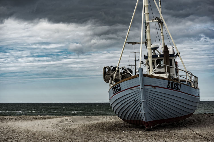 Boat on shore at beach against cloudy sky