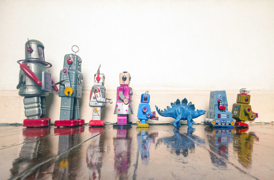 retro toys in a line on a wooden floor Lines Reflection Robots Copy Space Dionysus Flooring Fun Group Of Objects Humor In A Row Indoors  Large Group Of Objects Multi Colored No People Plastic Reflection Representation Still Life Studio Shot Toned Image Toy Toy Photography Variation Vintage Toys Water